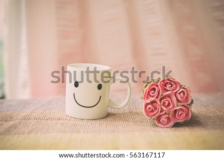 Happy cup on bed with bouquet of pink rose. Concept about happiness and waiting for someone. #563167117