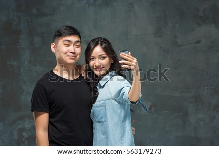 Portrait of smiling Korean couple on a gray #563179273