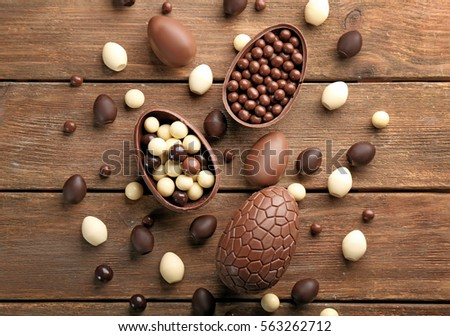 Chocolate Easter eggs and sweets on brown wooden background Royalty-Free Stock Photo #563262712
