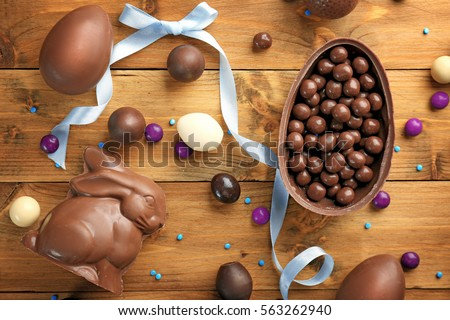 Chocolate Easter eggs, rabbit and sweets on wooden background Royalty-Free Stock Photo #563262940