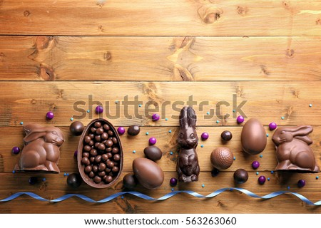 Chocolate Easter eggs, rabbits and sweets on wooden background Royalty-Free Stock Photo #563263060