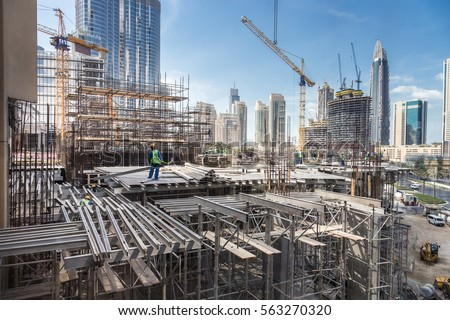 Laborers working on modern constraction site works in Dubai. Fast urban development consept. Royalty-Free Stock Photo #563270320