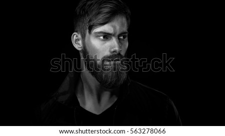 Black and white portrait of bearded handsome man in a pensive mood looking away #563278066