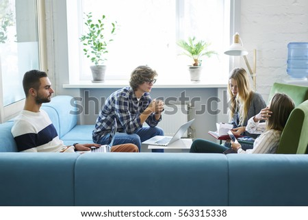 Team of skilled male and female journalist brainstorming during meeting sitting in modern interior office while monitoring latest news using laptop computer and free wireless connection to internet
