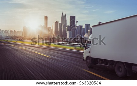 Truck traveling on road at sunrise - speed and delivery concept. #563320564
