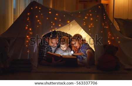 happy family father and children reading a book with a flashlight in a tent at home #563337706