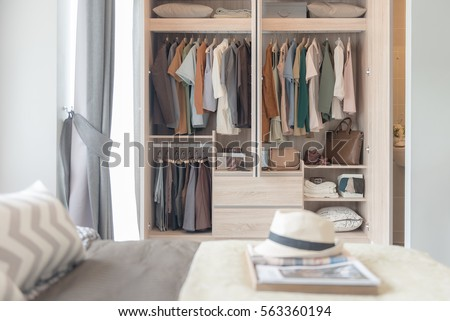 colorful clothes hanging on rail in wooden wardrobe #563360194
