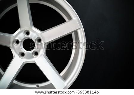 Closeup silver alloy wheel on black background #563381146