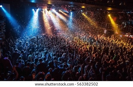 shiny rainbow confetti during the concert and the crowd of people silhouettes with their hands up. Dark background, smoke, concert  spotlights. Bright lights #563382502