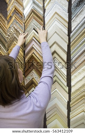 Female choosing a frame for picture in a framing workshop, vertical closeup #563412109