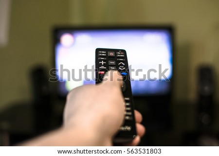 Remote control in hand in front of TV. Couch potato. #563531803