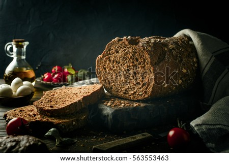 Whole grain bread on wooden cutting board with olive oil, tomato and basil . Dark toned photo with copy space. #563553463