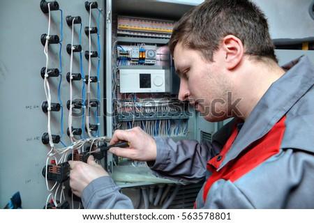 St. Petersburg, Russia - March 5, 2013: Mechanical Engineer doing upgrade equipment electrical switchboard. #563578801