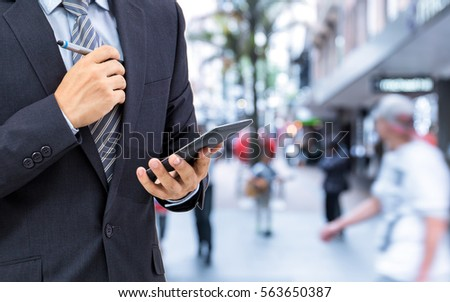 isolated business man hold the smartphone on the street  #563650387