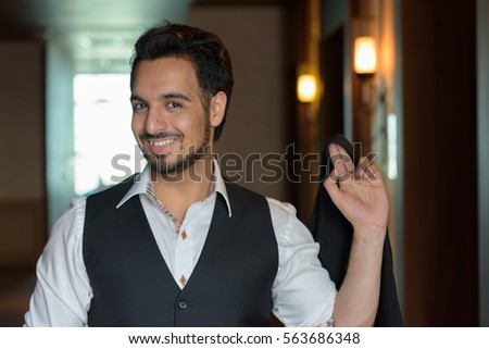 Young happy Indian man smiling while holding jacket in the corridors of hotel #563686348