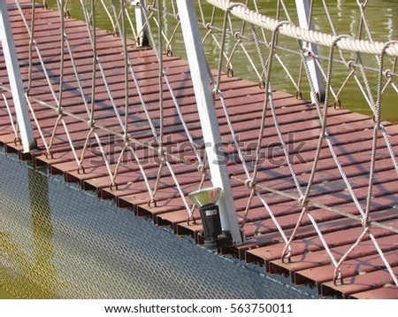The wooden bridge suspended by ropes #563750011