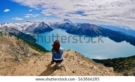 Woman doing yoga above alpine lake. Panorama Ridge. Garibaldi Lake. Garibaldi Provincial Park. Whistler. British Columbia. Canada. Royalty-Free Stock Photo #563866285