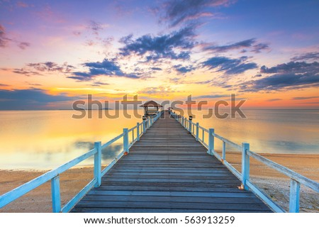 Old wood bridge pier  against beautiful sunset sky use for natural background ,backdrop and multipurpose sea scene #563913259