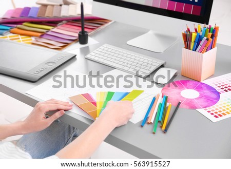 Young designer choosing color of interior while working in office, closeup #563915527