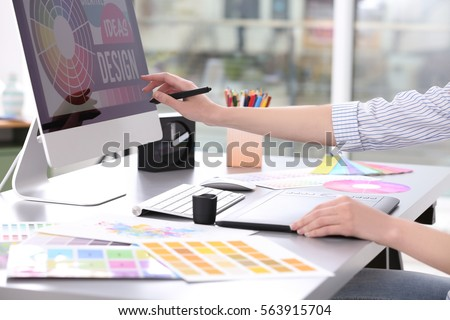 Young designer drawing sketches on graphic tablet, closeup Royalty-Free Stock Photo #563915704