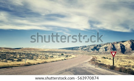 Retro color toned road with yield sign, travel concept picture, USA.