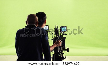 Photographer team and film crew and movie camera and green screen studio. #563974627