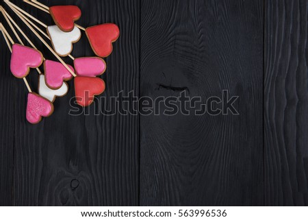 Gingerbreads for Valentines Day or wedding theme on black wooden background #563996536