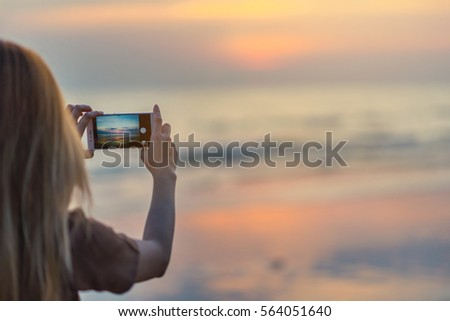 woman hands holding mobile phone to taking sunset photo, on the beach