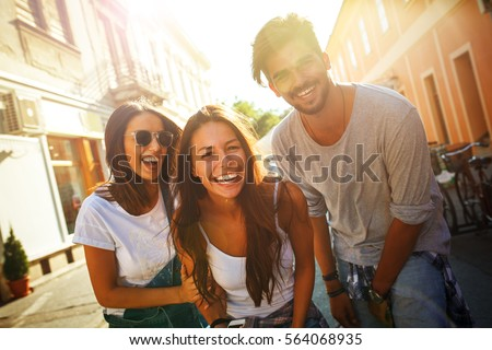 Group of happy young friends having fun on city street.Sunset.Close up image. #564068935