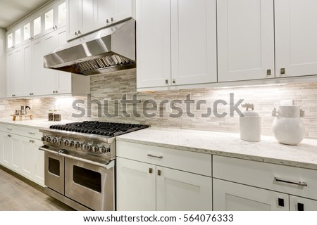 Gourmet kitchen features white shaker cabinets with marble countertops paired with stone subway tile backsplash and stainless steel hood over eight burner gas range. Northwest, USA Royalty-Free Stock Photo #564076333