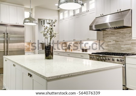 Gourmet kitchen features white shaker cabinets with marble countertops, stone subway tile backsplash, double door stainless steel refrigerator and gorgeous kitchen island. Northwest, USA #564076339