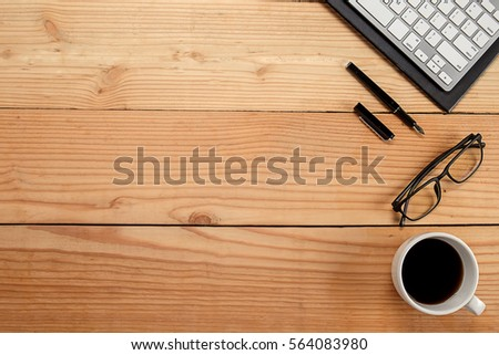 Office desk table with keyboard, notebook, pen and cup of coffee. Top view with copy space (selective focus). #564083980