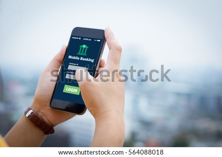 Female hands hold mobile banking on smart phone on blurred urban city as background Royalty-Free Stock Photo #564088018