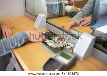 people, withdrawal, saving and finance concept - clerk giving cash money to customer at bank office or currency exchanger Royalty-Free Stock Photo #564103672