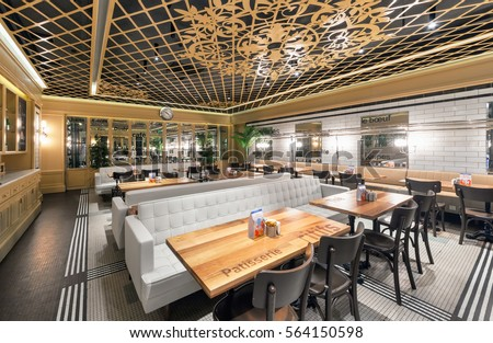 """MOSCOW - AUGUST 2014: Interior of a Turkish chain restaurant """"Kitchenette"""". Room full of mirrors, tables and long leather sofas #564150598"""