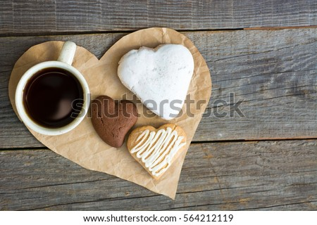Heart shaped cookies (big and small as couple), cup of coffee, bouquet of flowers decoration. sunny morning. Romantic breakfast or Valentine's Day Breakfast. Toned image