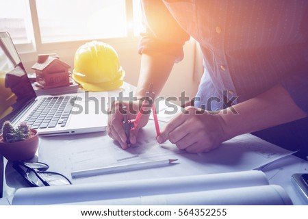 Architect working on blueprint. Architects workplace - architectural project, blueprints, ruler, calculator, laptop and divider compass. Construction concept. Engineering  tools,selective focus Royalty-Free Stock Photo #564352255