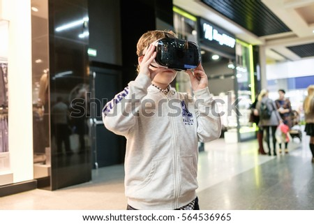 GRODNO, BELARUS - JANUARY 20, 2016: Boy wearing virtual reality glasses playing the game3D gadget headset goggles technology. Cardboard VR glasses  #564536965