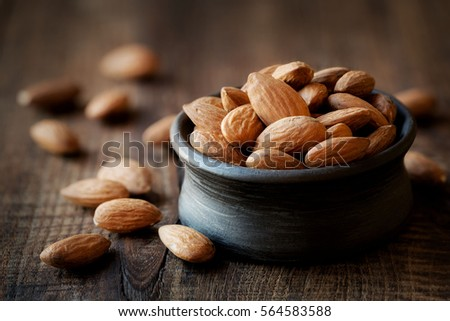 Almonds in a black bowl against dark rustic wooden background #564583588