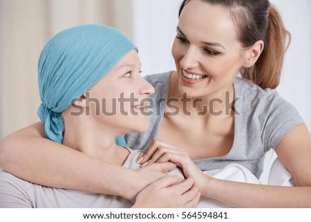 Hopeful cancer woman wearing headscarf, talking with friend