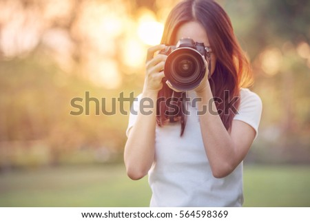 Woman is a professional photographer with dslr camera, outdoor and sunlight, Portrait, copy space.