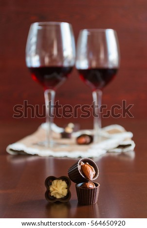 Two glasses of wine on a wooden table.  Candies. #564650920