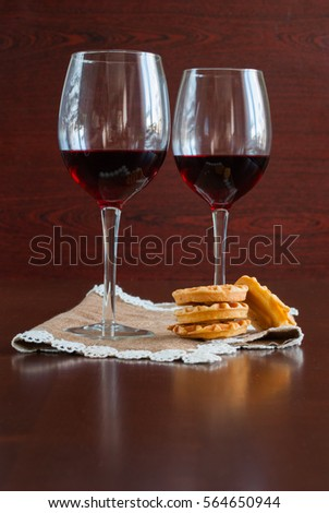 Two glasses of wine on a wooden table.  Waffles. #564650944