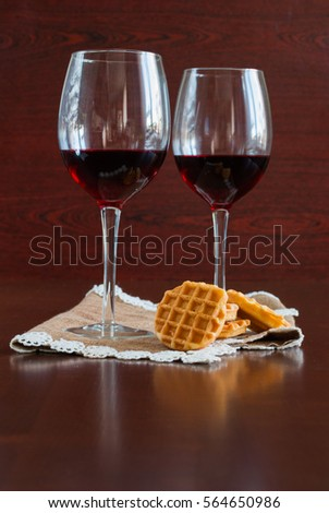 Two glasses of wine on a wooden table.  Waffles. #564650986
