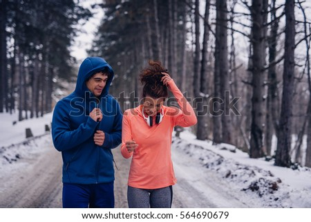 Photo of an athletic couple having fun on an early morning workout routine in the woods.