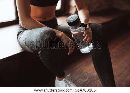 Cropped photo of attractive fitness woman sitting in gym and holding bottle of water. Royalty-Free Stock Photo #564703105
