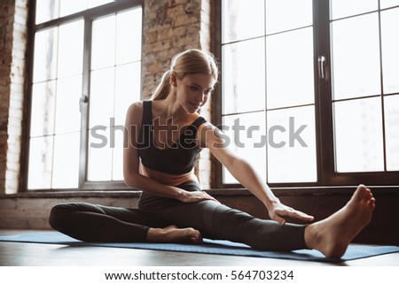 Image of gorgeous young fitness woman sitting in gym near window while make stretching exercises. #564703234