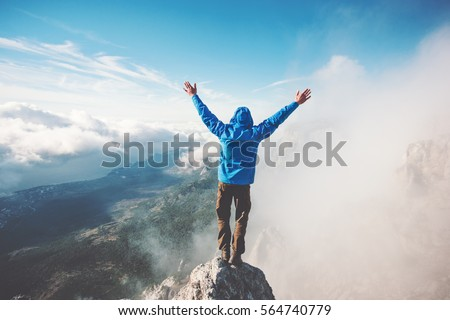Man Traveler on mountain summit enjoying aerial view hands raised over clouds Travel Lifestyle success concept adventure active vacations outdoor happiness freedom emotions Royalty-Free Stock Photo #564740779