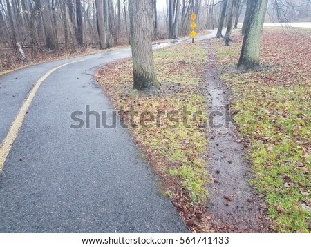 curved asphalt bike trail with straight shortcut trail through the grass Royalty-Free Stock Photo #564741433