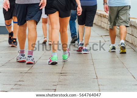 Several people walk down a sidewalk doing exercise #564764047